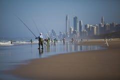 Mensen die op strand vissen Stock Foto's