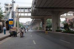Mensen die op vervoer op een weg in Lahore, Pakistan wachten Stock Foto's