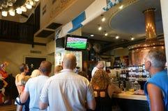 Mensen die op voetbal in restaurant letten stock fotografie