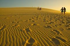 Mensen die op zandduinen lopen Stock Foto