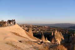 Mensen die op zonsopgang met ballons op klip in Goreme letten Cappadocia Turkije Stock Fotografie