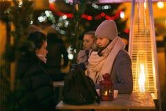 Mensen die in openlucht Kerstmisstempel op Kerstavond nippen Royalty-vrije Stock Foto's