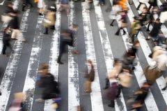 Mensen die over een voetgangersoversteekplaats lopen stock foto