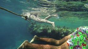 Mensen die over koralen met vissen in overzees zwemmen stock videobeelden