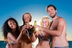 Mensen die partij hebben bij strand met dranken Stock Foto