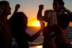 Mensen die partij hebben bij strand met dranken stock fotografie