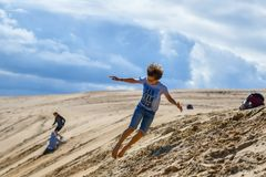 Mensen die pret op zandstrand hebben met zandduinen tijdens vakanties stock afbeelding