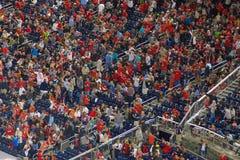 Mensen die in rood tijdens een gebeurtenis toejuichen stock foto