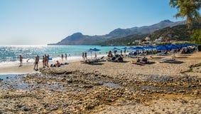 Mensen die rust op zandig strand van Plakias-stad hebben bij het eiland van Kreta Stock Foto's
