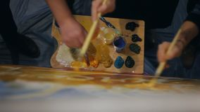 Mensen die samen met penselen op het witte canvas schilderen stock videobeelden