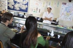 Mensen die Sushi in Japans Restaurant hebben Royalty-vrije Stock Foto's
