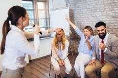 Mensen die team opleidingsoefening maken tijdens team de bouwseminarie het zingen karaoke Binnen de teambouw activiteiten stock foto