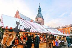 Mensen die traditionele herinneringen kopen bij een Europese Kerstmismarkt in Oud Riga, Letland royalty-vrije stock foto