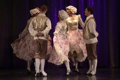 Mensen die in traditionele kostuums op stadium dansen, Stock Foto's