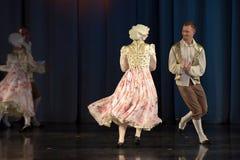 Mensen die in traditionele kostuums op stadium dansen, Stock Foto