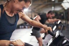 Mensen die trainig op exercycle in gymnastiek doen Stock Foto's