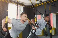 Mensen die TRX-opleiding in gymnastiek uitvoeren stock foto