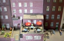 Mensen die van de zomer op een balkon in een miniatuurwereldopstelling genieten royalty-vrije stock afbeelding