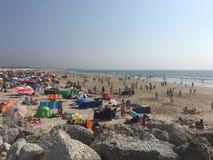 Mensen die van de zon genieten bij het strand Stock Foto