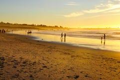 Mensen die van een gouden Strand genieten bij zonsondergang Stock Afbeelding