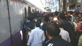 Mensen die van een trein bij een overvol station in Mumbai opstappen stock video