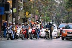 Mensen die in verkeerslichten in Hanoi, Vietnam wachten stock foto's
