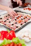 Mensen die verse Italiaanse pizza dicht omhoog koken stock afbeelding