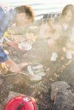 Mensen die vlees op picknick roosteren stock fotografie