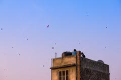 Mensen die vliegers van hun daken in de oude stad van Delhi vliegen Jaipur stock foto's