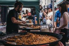 Mensen die voedsel kopen van een marktkraam in Portobello-Road Markt stock afbeeldingen