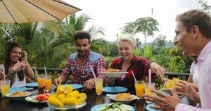 Mensen die voedsel overgaan die op terras jonge vrienden eten die zitting spreken bij lijst in openlucht mededeling stock video