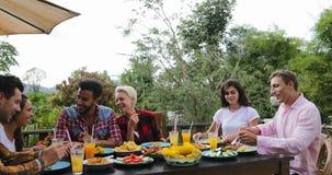 Mensen die voedsel overgaan die op terras jonge vrienden eten die zitting spreken bij lijst in openlucht mededeling stock footage