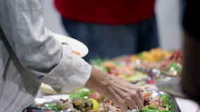 Mensen die voedsel van een buffet nemen stock video