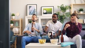 Mensen die voetbal op spel op TV ondersteunend dan ongelukkig en boos het voelen letten stock video
