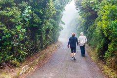 Mensen die in voetpad door regenwoud in Costa Rica lopen Royalty-vrije Stock Foto