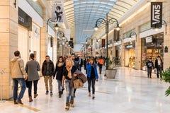 Mensen die voor Kerstmis in Luxewinkelcomplex winkelen Stock Foto