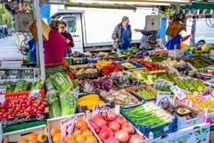 Mensen die vruchten en groenten kopen bij marktkraam in Portobello-Road Markt, Notting-Heuvel, het Verenigd Koninkrijk royalty-vrije stock afbeeldingen