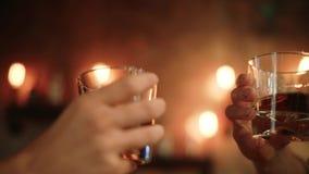 Mensen die whiskyglazen op barachtergrond clinking in langzame motie stock footage