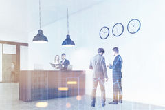 Mensen die zich dichtbij een bureauteller bevinden met drie gestemde klokken, Royalty-vrije Stock Afbeelding