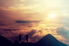 Mensen die zich op de bovenkant van de berg boven de wolken bevinden Suc Royalty-vrije Stock Foto's