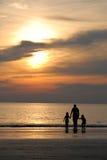 Mensen die Zonsondergang door strand bekijken Stock Fotografie