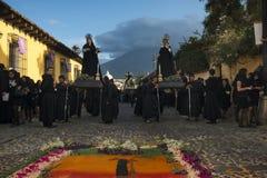 Mensen die zwarte robes in een straat van de oude stad van Antigua dragen tijdens een optocht van de Heilige Week in Antigua, Gua Royalty-vrije Stock Foto