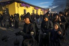 Mensen die zwarte robes in een straat van de oude stad van Antigua dragen tijdens een optocht van de Heilige Week in Antigua, Gua Royalty-vrije Stock Afbeeldingen