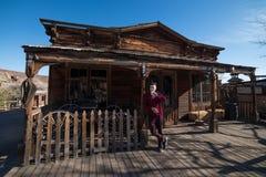 Mensen drinkwater voor oud blokhuis in het dorp van de cowboysprovincie stock foto