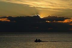 Mensen in een boot op een zonsondergangachtergrond Royalty-vrije Stock Afbeeldingen