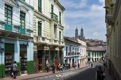 Mensen in een straat in het historische centrum van de stad van Quito, in Ecuador, met de Basiliek van de Nationale Gelofte op ba Stock Foto