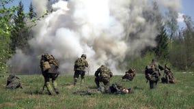 Mensen in eenvormig op achtergrond van de militaire explosie van de handgranaat in bos stock footage
