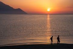 Mensen en een berg als silhouet bij een waterfront stock foto