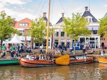 Mensen en historische boten in oude haven tijdens de Dagen van gebeurtenisadmiraliteit, Dokkum, Friesland, Nederland stock foto's