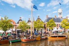 Mensen en historische boten in oude haven tijdens de Dagen van gebeurtenisadmiraliteit, Dokkum, Friesland, Nederland stock foto